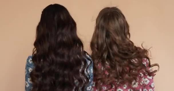 View from back of girls in light dresses with long hair