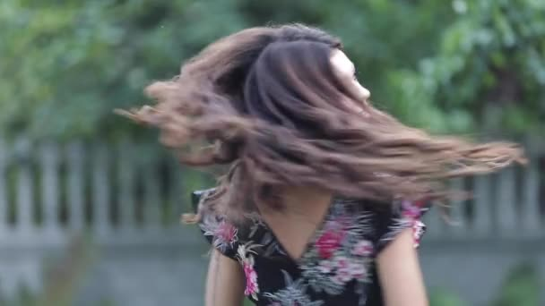 Childish girl in floral dress laughing and twirling around