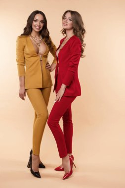 Two gorgeous models in colored suits and high heels over flat background.