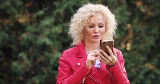 Blondine schaut aufs Handy, bekommt Nachricht und lacht