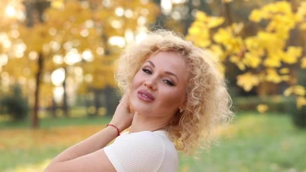 Gyönyörű szőke nő megérintette a göndör haj, őszi park séta.