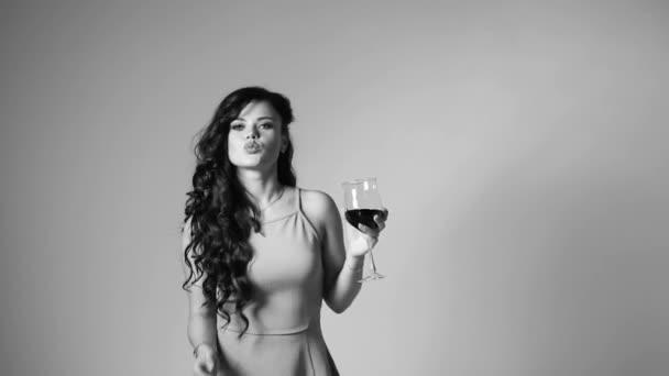 atemberaubende elegante Mädchen tanzen mit einem Glas Wein im Studio.