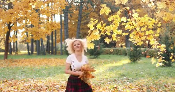 Happy blonde woman in sexy crop top and skirt playing with foliage in park.
