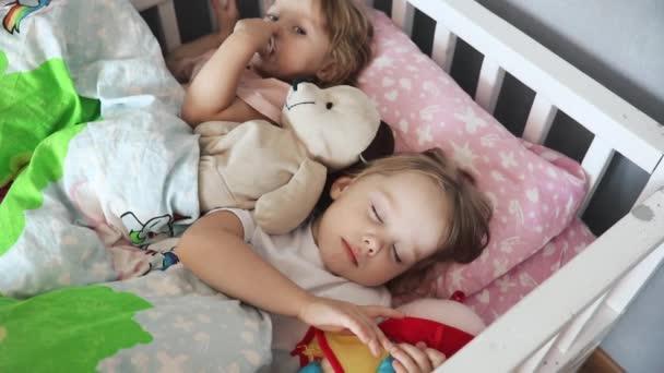 Dvě milé sestry spí ráno v posteli.