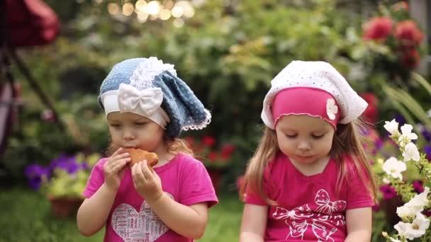 Aranyos kislány nyáron kalapot eszik finom sütiket a kertben.