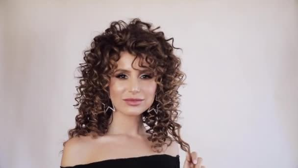 Sexy young woman with curly hair looking at camera.