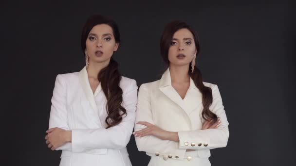 Női ikrek fehér öltönyök pózol, míg konfetti alá