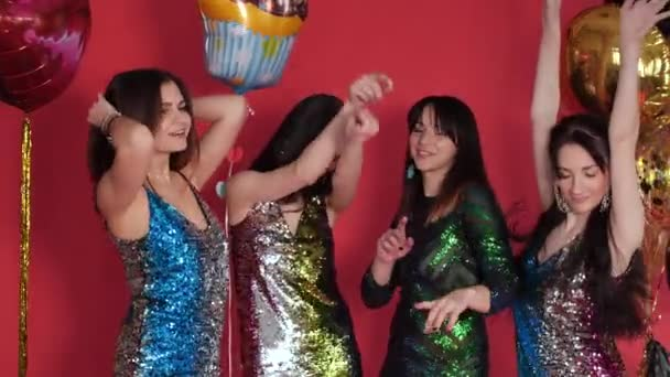 Four amazing girls in sparkling dresses dancing at party.