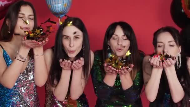 Trendy ladies in sparkling dresses blowing air kisses at camera.