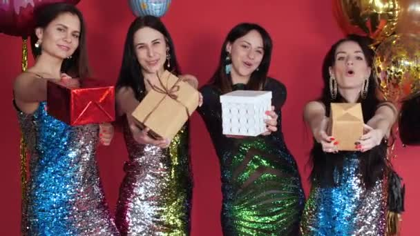 Happy four women in bright short dresses keeping gifts