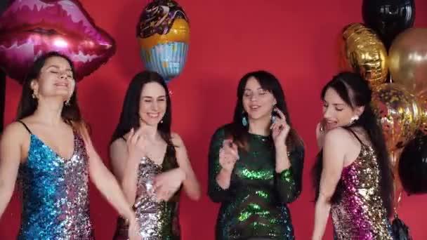 Šťastné čtyři ženy v jasných krátkých šatech, které drží dary