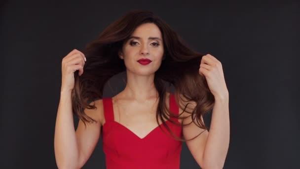 Gyönyörű barna lány, aki ő hosszú haja mindkét kezével.