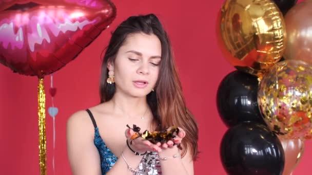 Boldog nő fúj csillogó konfetti a kamera