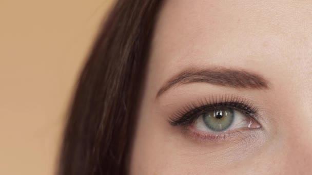 abgeschnittene Aufnahmen attraktiver junger Frau mit künstlichen Wimpern, die lächelt.