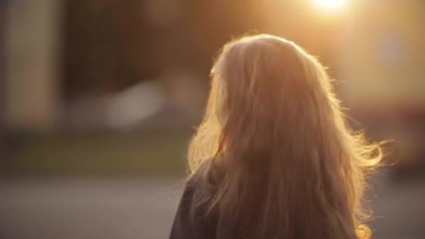 Dívka se kroucení a pózování s nádherými dlouhými vlasy v parku