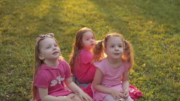 Three girls sitting on grass in park and laughing