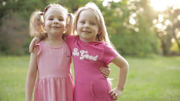Cute young children in pink dresses hugging and smiling at camera in park.