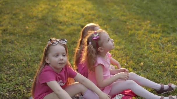 Tři dívky sedí na trávě v parku a smějí se
