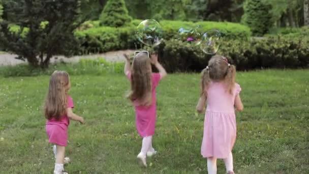 Boldog kislányok játszanak a kertben és a játék buborékok
