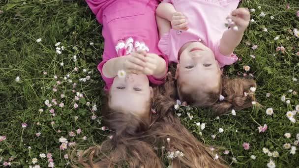 Két aranyos kislány feküdt fejjel lefelé a rét fű és a virágok, hogy a levegő csók és integetett kézzel