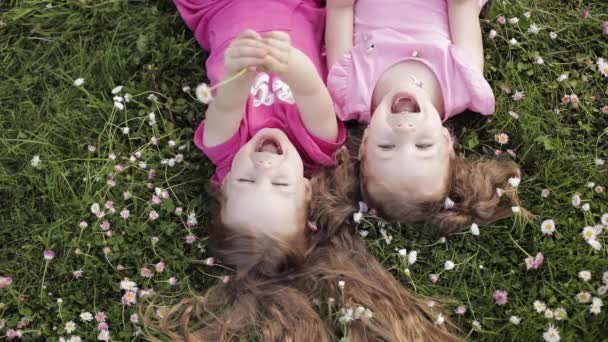 Dvě roztomilá holčička, ležící vzhůru nohama na travnatou trávu a květiny, které dělají vzdušnou pusu a mávající ruku