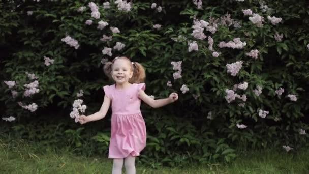 Boldog nevetve vicces kis baba lány jumping nyári kert lassított