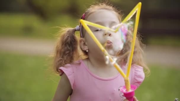 Confident playful little cute girl blowing huge air soap bubble blower medium close-up