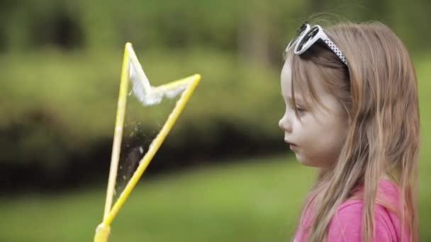 Magabiztos játékos kicsi ravasz lány fúj hatalmas levegő szappan buborék fúvó közeg zár-megjelöl