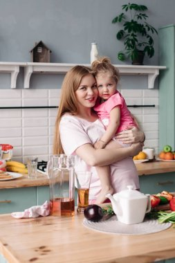 Happy beautiful mother with daughter in morning kitchen.