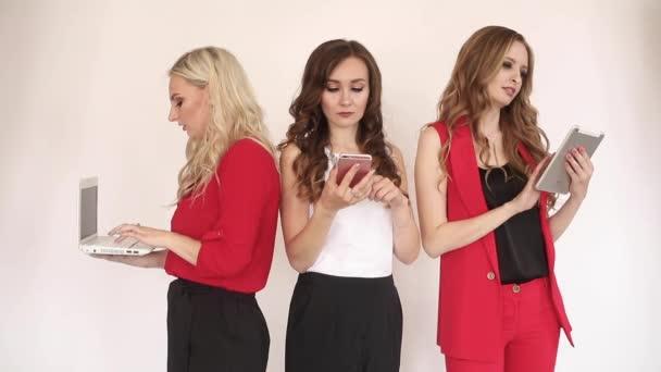 Elegantní ženy používající elektronická zařízení a vykřikují nahlas.