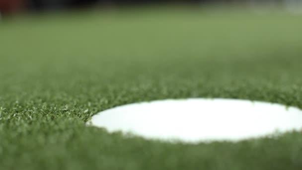 Uzavření malé golfové koule do díry hrající profesionální Sport golfingu