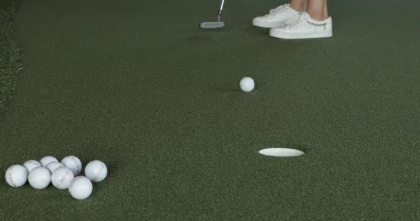 Někdo střílí díru v golfu.