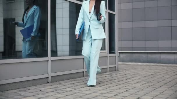 Businesswoman carrying a folder and a paper cup