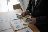 Mladý asijský obchodník, který stojí a počítá dolarovou bankovku ze svého stolu. Koncept obchodních výsledků
