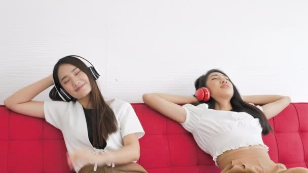Two Asian teenage girls sitting on red couch and listening to music from smartphone with headphones in home. beautiful woman relaxing lying and lifestyle concept.