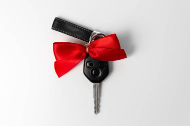 Car keys with red bow as present on white background. New car gi