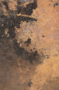 Texture of a burnt surface rusting away in orange.