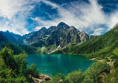 View on the turquoise color lake between high and rocky mountains. Beautiful alpine landscape.