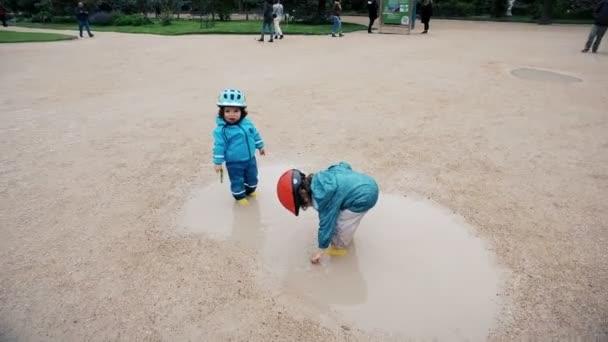 Děti hrají v malé vodní jezírko v Jardin des rostlin v Paříži před Muzeum přírodní historie a geologie galerie