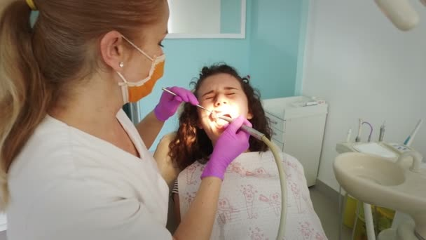 Dentist making professional teeth cleaning female young patient at dental office