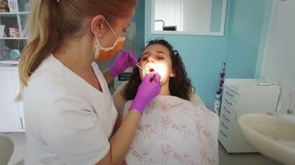 Zubař, že profesionální zuby čištění mladá pacientka v zubní ordinaci