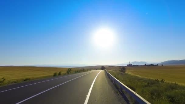 Řídit zakřivené venkovských asfaltové silnici mezi sklizní zemědělství pole