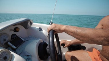 Close up of skippers hands turning steering wheel at sailing boat
