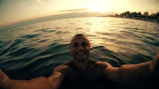 Selfie of happy man smiling and having fun enjoying summer vacation at sunset, sunrise