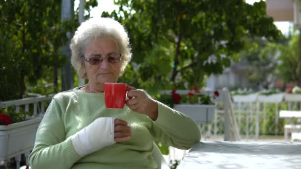 elderly old woman with injured hand drinking coffee outdoor sitting