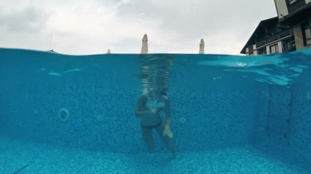 Young teen with googles diving in outdoor pool, gopro dome shot, SLOW MOTION