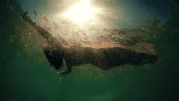Woman floating on water at sunset, bottom of the sea POV