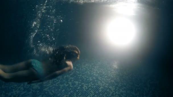 Female swimming mermaid underwater toward light in dark pool