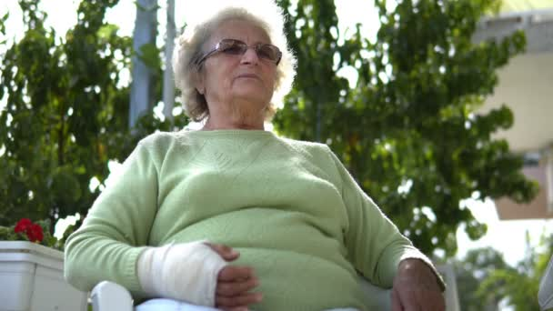 Portrait of elderly old woman with injured hand broken arm sitting and talking
