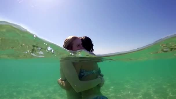 Beautiful young teenage girl friend have fun hugging each other on vacation, gopro dome half underwater view, SLOW MOTION